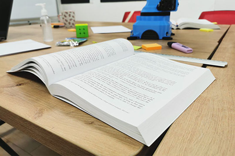 Programming manual in English, open on a table in a classroom
